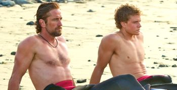 Chasing Mavericks stars Gerard Butler and Jonny Weston relax on a beach