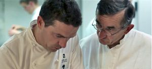 Step Up to Plate where Michel and Sebastien Bras confer in kitchen