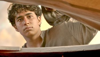 Suraj Sharma as Pi checks on the tiger in his lifeboat