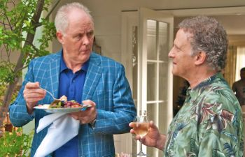 John Lithgow and Albert Brooks converse at a birthday party