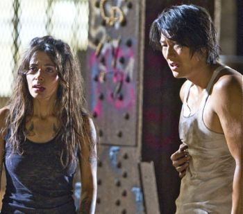Sarah Shahi aand Sung Kang confront bad guys in warehouse
