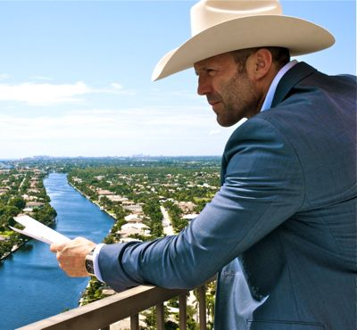 Parker's Jason Statham gazes at Palm Beach from balcony