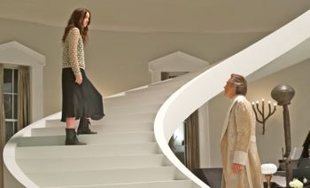 Alice Englert ascends staircase as Jeremy Irons looks on