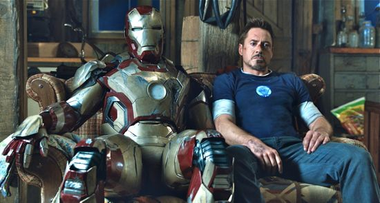 Robert Downey Jr as Tony Stark sits beside his Iron Man suit