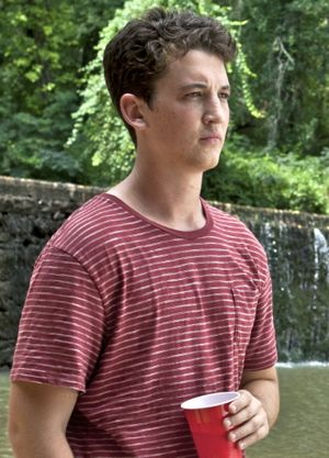 Miles Teller gazes at a river