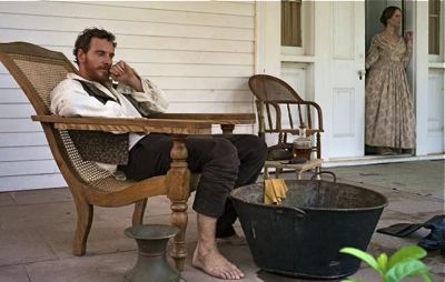 Michael Fassbender sits on planatation mansion porch to watch his slaves