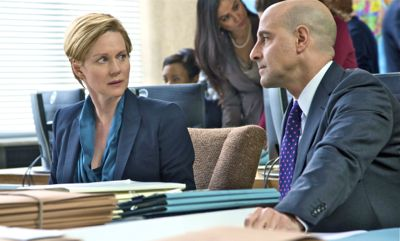 5th Estate's Laura Linney and Stanley Tucci look at each other at conference table