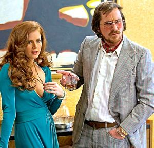 American Hustle's Amy Adams and Christian Bale stand in front of painting