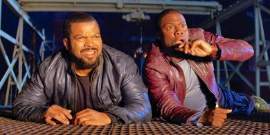 Ride Along's Ice Cube and Kevin Hart look out from hiding place