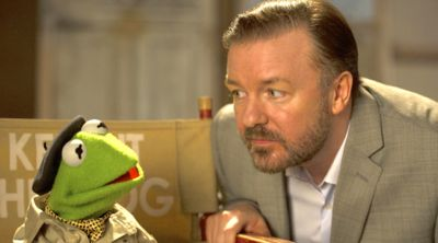 Ricky Gervais leans down next to Kermit the Frog