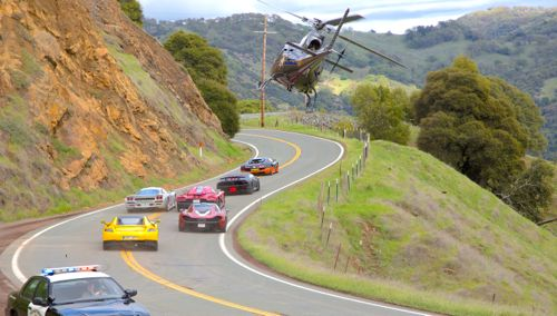 Need for Speed's cars race around a bend pursued by cops