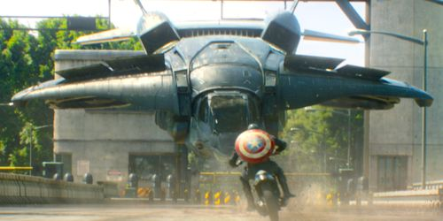 Marvel's Captain America rides cycle directly at fighter jet hovering over road