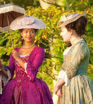 Belle's Gugu Mbatha-Raw holds parasol and smiles at companion
