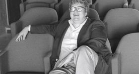 Roger Ebert sits in a screening room