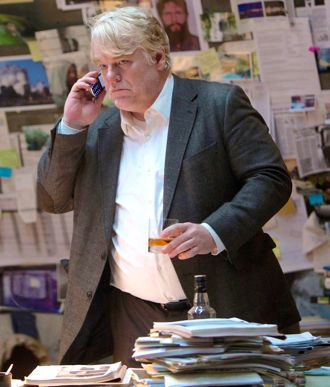 Most Wanted Man's Philip Seymour Hoffman taks on phone behind his desk