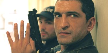 Lucy's Amr Waked with pistol takes cover behind hospital wall