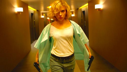 Lucy's Scarlett Johansson walks hotel corridor with two guns