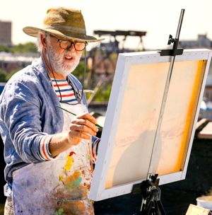 Love is Strange's John Lithgow paints canvas on a rooftop