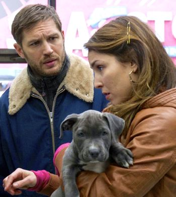 Drop's Noomi Rapace, holding puppy, and Tom Hardy shop in pet store