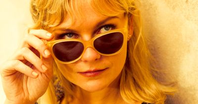 Two Faces of January's Kirsten Dunst lowers sun glasses and glances right