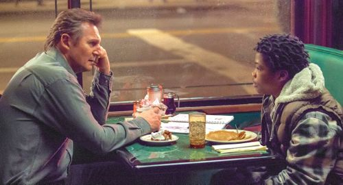 """Liam Neeson discusses his case with Brian """"Astro"""" Bradley at coffee shop table"""