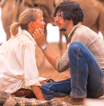 Mia Wasikowska crouches and talks to Adam Driver beside camels in desert