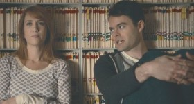 Kristen Wiig and Bill Hader lean back against bookcase