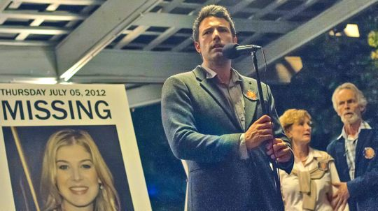 Gone Girl's Ben Affleck stands next to poster of missing wife
