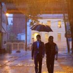 In Revenge of the Green Dragon two men walk on dark, rainy street