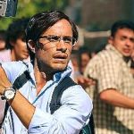 Rosewater's Gael Garcia Bernal holds camera during Tehran street demonstration