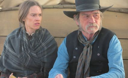 Homesman's Hilary Swank and Tommy Lee Jones ride up front in covered wagon