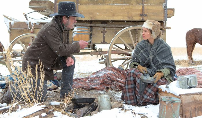 Homesman's Tommy Lee Jones and Hilary Swank talk as they squat at snowy campsite