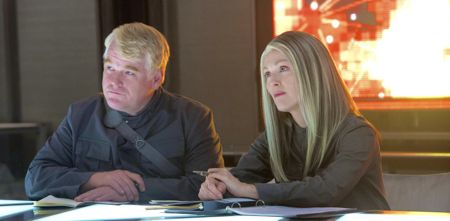 Hunger Games' Philip Seymour Hoffman and Julianne Moore sit at table in underground room