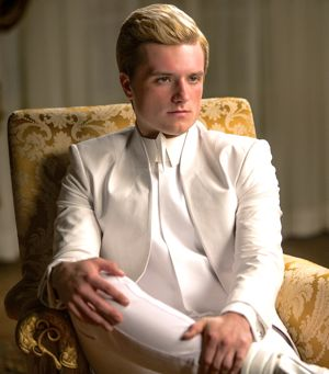 Hunger Games' Josh Hutcherson in white suit sits uncomfortablly in chair