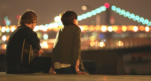 Song One's Anne Hathaway, Johnny Flynn sit gazing at nighttime Manhattan from Brooklyn riverfront