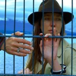 Goodbye to Language's Heloise Godet looks through fence bars as a hand reaches out from left