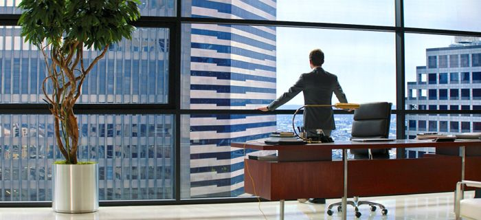50 Shades of Grey's Jamie Dornan stares out of glass enclosed high rise office building
