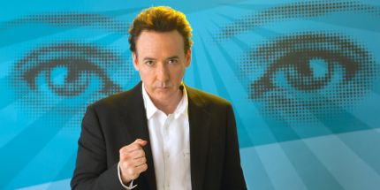 Maps to Stars' John Cusack as self-help guru stands before huge eyes on a blue background