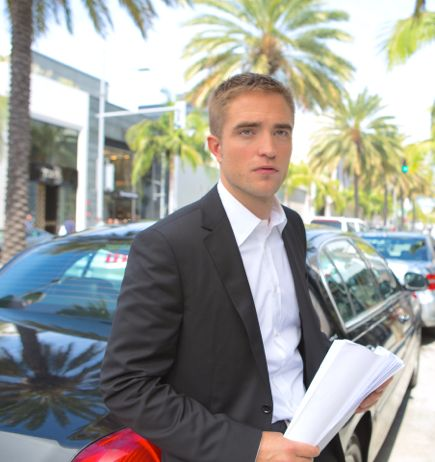 Maps to the Star's Robert Pattinson stands beside town car on Beverly Hills street
