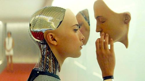 Ex Machina's Alicia Vikander stares at and touches a human mask on wall