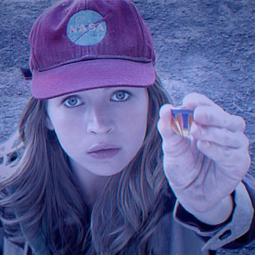 Tomorrowland's Britt Robertson holds up pin with large T