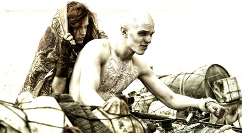 RILEY KEOUGH as Capable and NICHOLAS HOULT as Nux ride atop scavanger vehicle