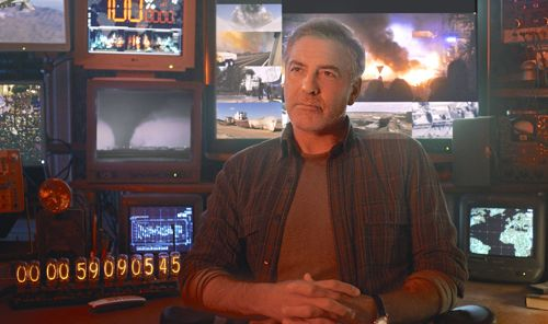 Tomorrowland's George Clooney sits in front of wall of TV monitors