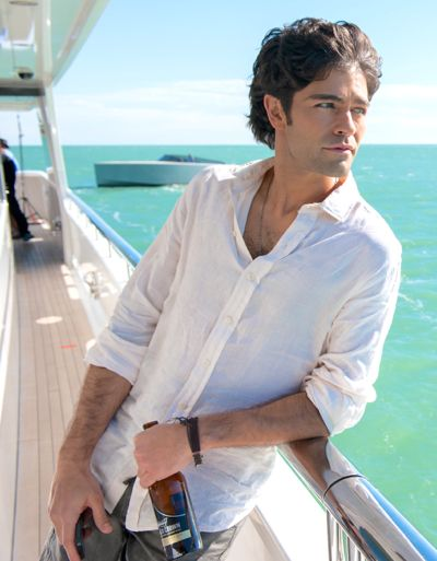 Entourage's Adrian Grenier holds wine bottle and stares out to sea from yacht