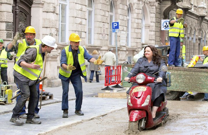 Spy's Melissa McCarthy rides motorbike through wet cement surrounded by construction workers