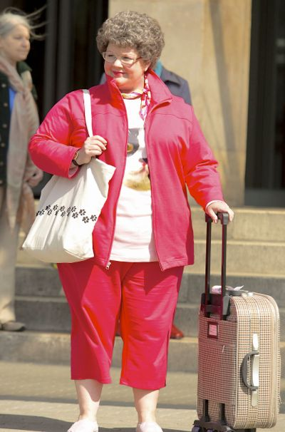 Spy's Melissa McCarthy stands on street with luggage and in frumpy disguise