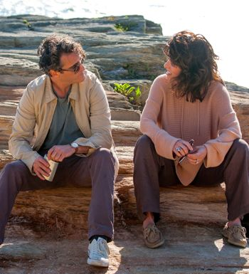 Irrational Man's Joaquin Phoenix talks to Parker Posey sitting on lakeside rocks