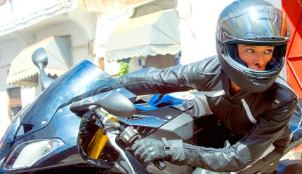 Mission Impossible's Rebecca Ferguson watches opponents as she turns her motorbike