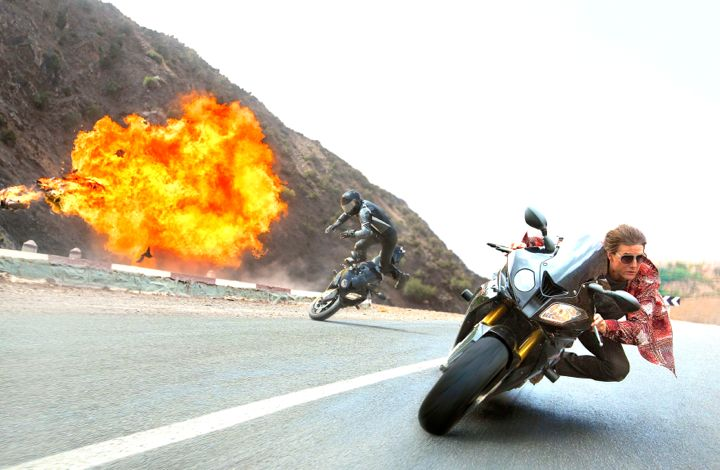 Mission Impossible's Tom Cruise races down road of explosions on motorbike