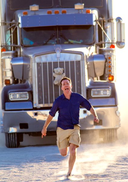 Vacation's Ed Helms runs frantically in front of a big rig